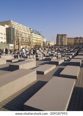 BERLIN, GERMANY - NOV 12: Visitors visit The Holocaost memorial on Nov 12, 2011 in Berlin, Germany. This place consist of 2,711 different size of concrete blocks placed on 19.000 sq.metres area. - stock photo