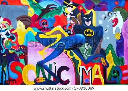 BERLIN, GERMANY - NOVEMBER 10, 2013: Fragment of the East Side Gallery exhibition, the largest outdoor art gallery in the world, painted on the segment of Berlin wall - stock photo