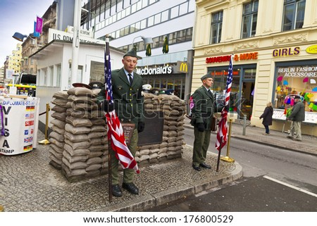 BERLIN, GERMANY-NOVEMBER 8, 2013: Unidentified young men dressed as American soldiers stand in front the Check Point Charlie - one of checkpoints of the U.S. to the Soviet occupied zone during WW2. - stock photo