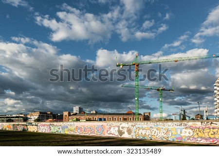 BERLIN, GERMANY - SEPTEMBER 28, 2015:  Building activity along the East Side Gallery in Berlin, Germany. The East Side Gallery is the longest preserved stretch of the Berlin wall and was painted by - stock photo