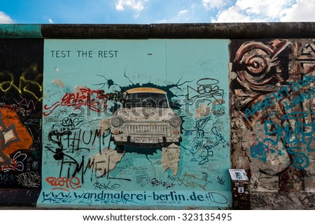 BERLIN, GERMANY - SEPTEMBER 28, 2015:  Graffiti showing a Trabi (Trabant car) at the East Side Gallery in Berlin, Germany. The East Side Gallery is the longest preserved stretch of the Berlin wall and - stock photo