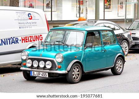BERLIN, GERMANY - SEPTEMBER 10, 2013: Green Austin Mini Cooper retro vehicle at the city street. - stock photo