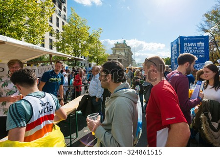 BERLIN, GERMANY - SEPTEMBER 27, 2015: Participants of the Berlin Marathon 2015 are getting their medals after the finish line at the famous Brandenburg Gate on a lovely autumn day in Berlin, Germany. - stock photo