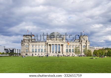 Berlin, Germany - September 9, 2015: People enjoying a warm autumn day on the lawn in front of the Reichstag, German Parliament.