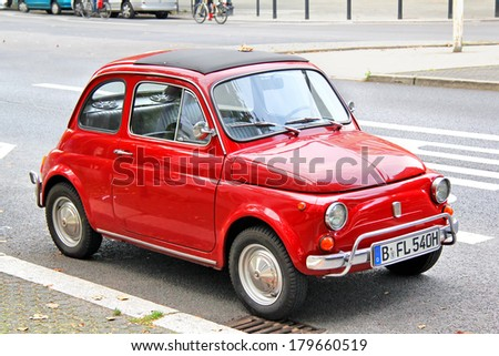 BERLIN, GERMANY - SEPTEMBER 12, 2013: Red Fiat 500 retro car at the city street. - stock photo