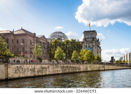 BERLIN, GERMANY - SEPTEMBER 27, 2015: View on the Reichstag building in Berlin from the river Spree on a bright autumn day. The area around the Reichstag is pretty busy on this day since the landmark - stock photo