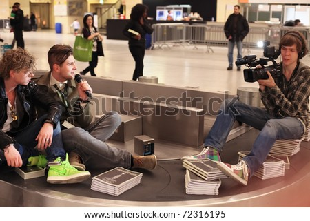 BERLIN - JANUARY 21: Designer interviews on conveyor belt at Bread & Butter fair on January 21, 2011 in Berlin, Germany. Tens of thousands of visitors come each year. - stock photo