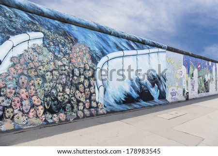 BERLIN - JANUARY 13, 2014 : The East Side Gallery is the largest outdoor art gallery in the world. Here it shows people, who break out through a gap of the wall. Artist was Kani Alavi. - stock photo