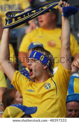 BERLIN - JUNE 15:  A Swedish supporter cheers prior to the start of a 2006 FIFA World Cup soccer match between Sweden and Paraguay June 15, 2006 in Berlin, Germany. - stock photo