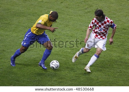 BERLIN - JUNE 13:  Adriano of Brazil (l) moves the ball against Niko Kovac of Croatia during a World Cup match June 13, 2006 in Berlin, Germany. Editorial use only.  No pushing to mobile device usage. - stock photo