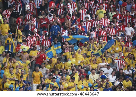 BERLIN - JUNE 15:  Sweden and Paraguay supporters in the stands prior to a 2006 FIFA World Cup soccer match between Paraguay and Sweden June 15, 2006 in Berlin, Germany. - stock photo