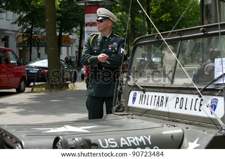 "BERLIN - MAY 28: A man in the form of a military police car and Willys MB, the exhibition ""125 car history - 125 years of history Kurfurstendamm"", May 28, 2011 in Berlin, Germany"