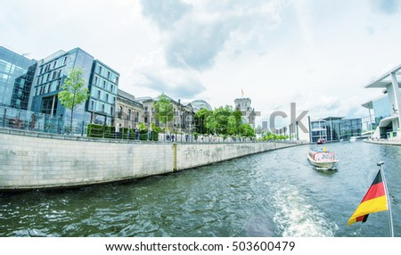 BERLIN - MAY 27, 2012: Tourists visit the modern buildings in Bundestag area along Spree river. The city has more than 26 million overnight stays every year.