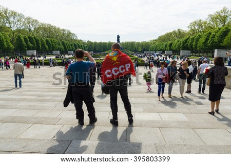 BERLIN - MAY 09, 2015: Victory Day in Treptower Park. The man with the flag of the Soviet Union is on the background of Soviet War Memorial.