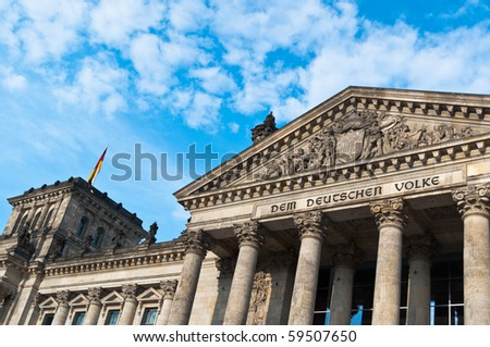 Berlin Reichstag (Germany's parliament building) with flags on a great cloudy summer day - stock photo