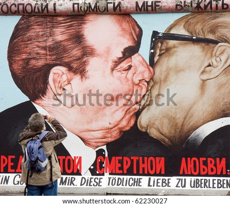 BERLIN - SEPTEMBER 26: Tourist takes photos with the famous kiss from the Berlin Wall containing now new designs Sept 26, 2010 in Berlin. - stock photo