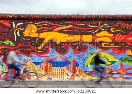 BERLIN - SEPTEMBER 26: Tourists visit the new designed Berlin Wall Sept 26, 2010 in Berlin. - stock photo