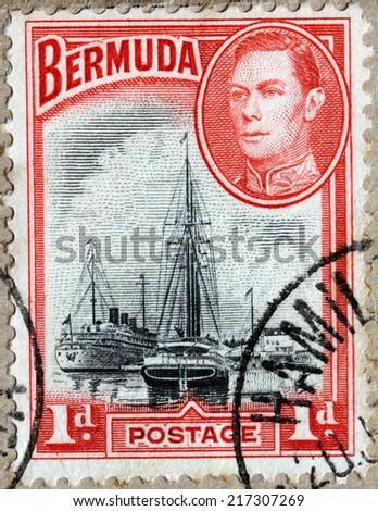 BERMUDA - CIRCA 1940: A stamp printed by BERMUDAS ISLES shows image portrait of King Georg VI and view of passenger ship Monarch of Bermuda and schooner J.W. Clice in Hamilton Harbor, circa 1940 - stock photo