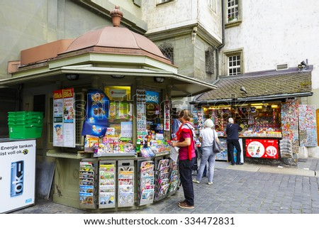 BERN, SWITZERLAND - SEPTEMBER 11, 2015: Unrecognized passerby do some shopping at a kiosk. Retail sales in heavily used areas provides daily access to many needed products and small gifts - stock photo