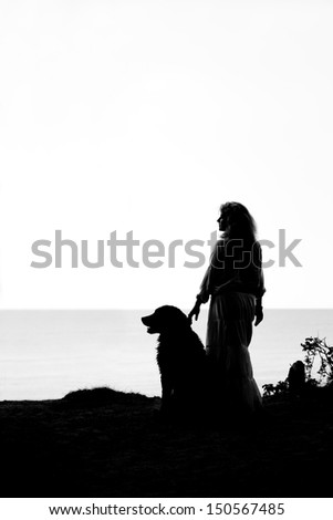 bernese mountain dog and woman silhouettes  looks aside at sea - stock photo