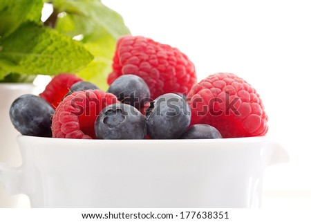Berries and peppermint dessert on white background - stock photo