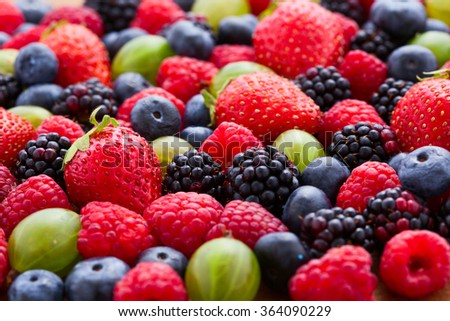 Berries Background macro, selective focus. Raspberries appetizing, natural blueberry, juicy strawberries, ripe gooseberries. Fruit Mix like bright background - stock photo