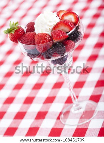 Berries in a glass on a checkered tablecloth