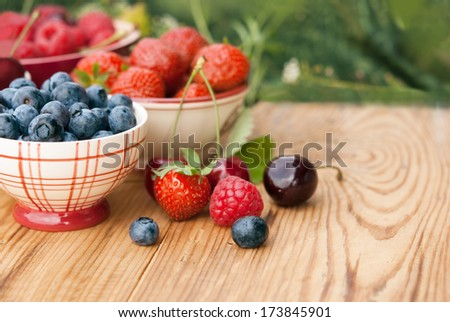 Berries in bowls on wooden table, fruits, cherry, raspberry, strawberry and blueberry - stock photo