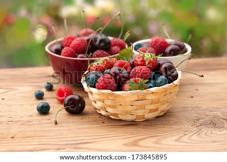 Berries in bowls on wooden table in a garden, fruits, cherry, raspberry, strawberry and blueberry - stock photo