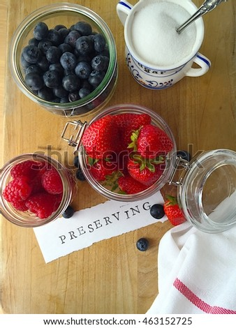 Berries in glass jars with preserving word