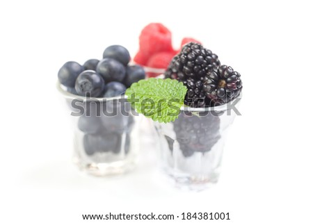 Berries in small glasses isolated over white - stock photo