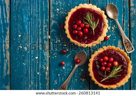 berries jam tarts decorated with cranberry and rosemary, top view