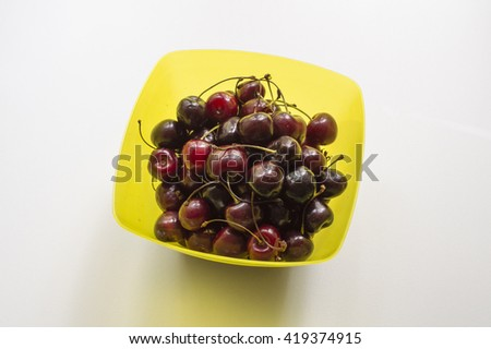 Berries of ripe cherry on a yellow dish