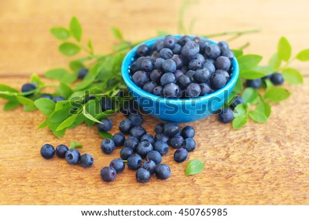Berries of ripe juicy bilberry in a blue small  plate on a wooden table. - stock photo