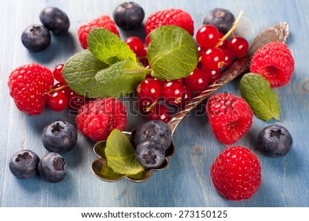 Berries on Blue Wooden Background. Summer or Spring Organic Berry over Wood. Raspberries, Blueberry, Red Currant, Vintage Spoon and Mint. Agriculture, Gardening, Harvest Concept. - stock photo