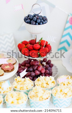 Berries, popcorn and canapes on a dessert table at party - stock photo