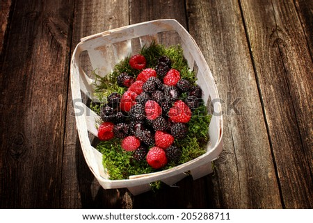 berries raspberries and blackberries in a basket on a wooden background - stock photo