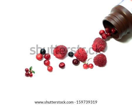 Berries spilling out of pills bottle - stock photo