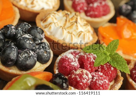 Berries tarts, peach and lemon tarts display - stock photo