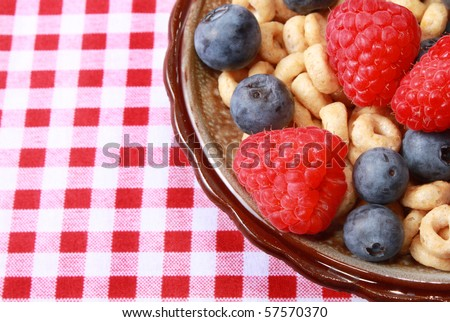 Berries with cereal and milk on checkered tablecloth