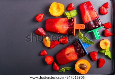 Berry and fruit ice cream pops on black surface, top view