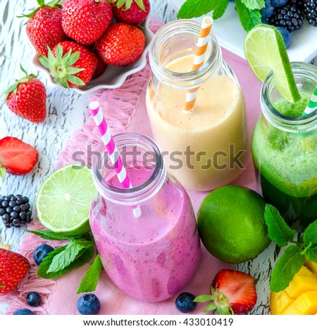 Berry and fruit smoothie in bottles, healthy summer detox yogurt drink, diet or vegan food concept, fresh vitamins, mango, lime, passion fruits - stock photo