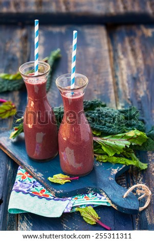 Berry and green leaves smoothie on wooden table - stock photo