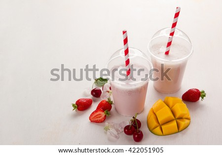 Berry  and ice cream milkshake (smoothie) with fresh berry  in plastic glass, selective focus
