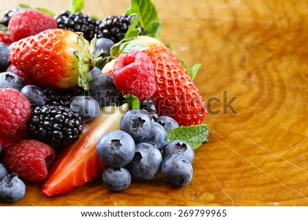 berry assortment on a wooden background - raspberries, blackberries, strawberries, blueberry  - stock photo