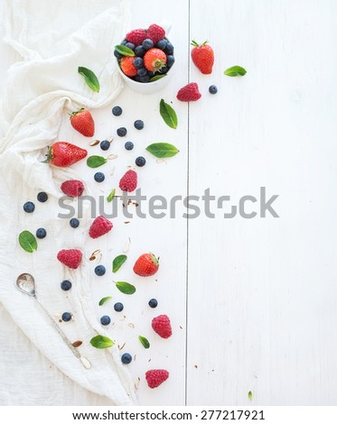 Berry frame with copy space on right. Strawberries, raspberries, blueberries and mint leaves, white wooden background, top view - stock photo