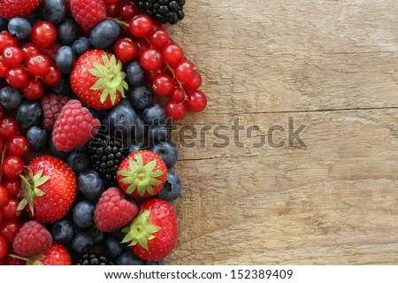 Berry fruits like strawberries, blueberries, red currants, raspberries and blackberries on a wooden board with copyspace - stock photo