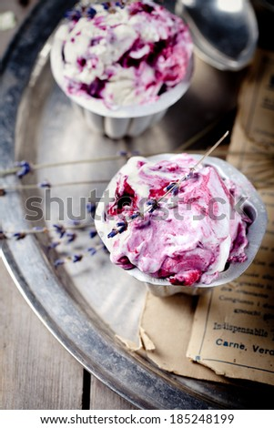 Berry ice cream in vintage metal cups on a old metal tray with lavender flowers on a wooden background - stock photo
