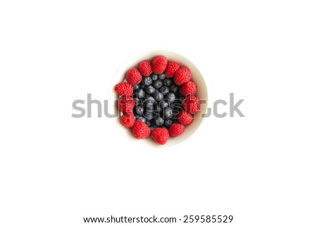 Berry is one of the most common fruit juicy bright colour. Title: Raspberries and blue berries in a white bowl on white background