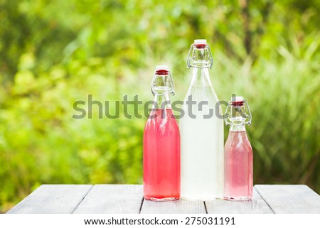 Berry lemonade in the bottles on the table outdoors - stock photo